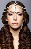 Beauty portrait of young woman with diadem. Brunette girl with long hair plaits and day female makeup on gray background