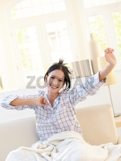 Happy attractive woman stretching in pyjama