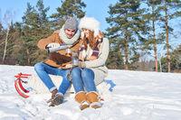 Glückliches Paar trinkt Tee zusammen im Schnee
