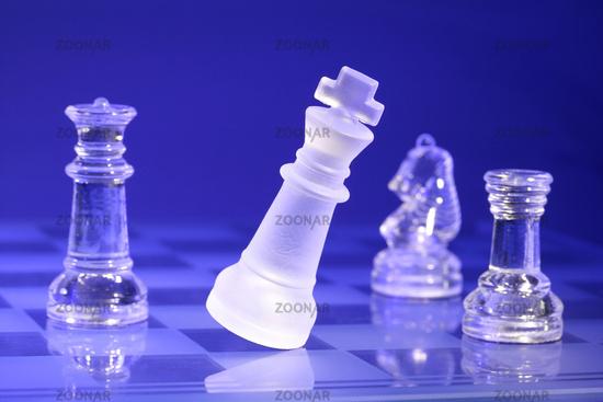 Glass chessmen in blue light, falling King