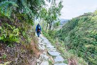 tourist on path on mountain slope in Dazhai