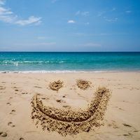 Smilinig face draw on the beach over sea