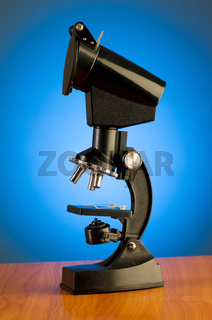 Microscope against blue gradient background