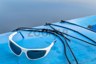 sport sunglasses on stand up paddleboard