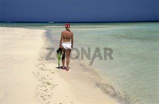 Junge Frau am weißen Strand geht Schnorcheln