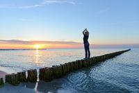 Frau macht Yoga im Sonnenuntergang am Meer