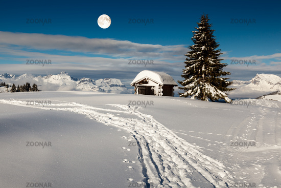 Full Moon above Small Hut and Fir Tree on the Top of the Mountain in Megeve, French Alps