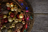Twig Christmas wreath with the center filled with ornaments and decorations on a rustic wood table,