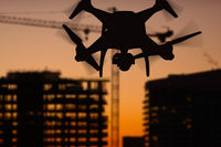 Silhouette of Unmanned Aircraft System (UAV) Quadcopter Drone In The Air Over Buildings Under Construction.