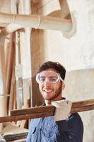 Handwerker trägt Holz in Werkstatt