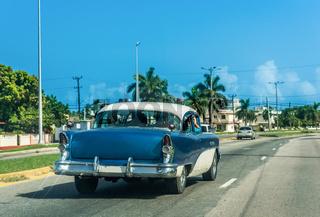 Blauer amerikanischer Oldtimer mit weissem Dach fährt durch Varadero Kuba - Serie Kuba Reportage