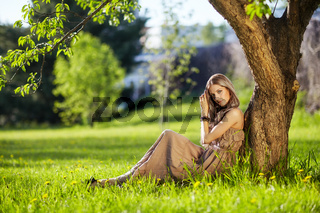 Beautiful young woman dressed in boho style sitting on green grass