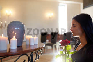 woman with rose and funerary urn at church