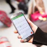 Woman checking calendar information on mobile phone sitting in airport terminal.