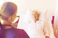 doctor or nurse visiting senior woman at hospital