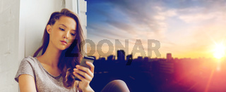 sad pretty teenage girl with smartphone texting