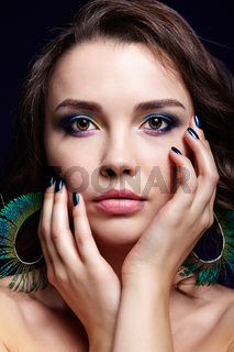 Portrait of beautiful brunette woman on black background and peacock feather earrings