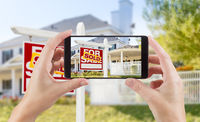 Female Hands Holding Smart Phone Displaying Photo of Sold For Sale Real Estate Sign and House Behind.