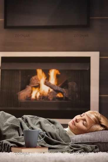 Woman sleeping beside fireplace