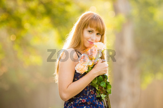 Beautiful young sexy girl standing with a bouquet of roses on a background of green sunny blurred