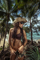 Beautiful brunette woman with straw hat and sunglasses in tropical forest