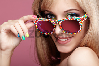 Young blonde smiling  woman with fun candy glasses on pink background
