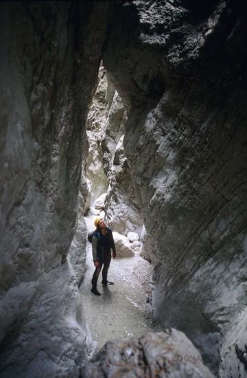 Eine Mann schaut sich beim Canyoning die enge Schlucht an