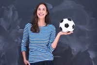woman holding a soccer ball in front of chalk drawing board