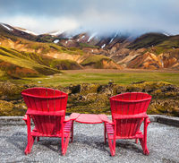 Two red chaise lounges connected by table