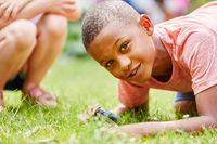 Kind erforscht mit Lupe die Natur