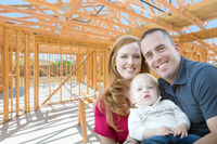 Young Military Family Inside The Framing of Their New Home at Construction Site.