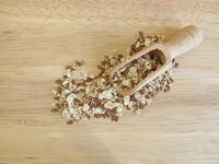 Seed mixture with rolled oats, flaxseeds and sesame on wooden board