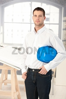 Young architect standing in bright office