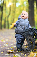 Baby boy with yellow autumn maple leaf