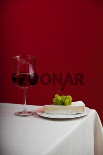 Glas Rotwein und Camembert mit Trauben