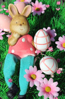 Liegender Osterhase mit bunten Eiern und Blumen