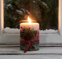 Christmas candle glowing on window sill with snowy evergreen branches outside
