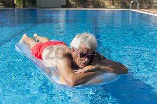 Senior man floating on water