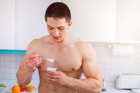 Gesunde Ernährung junger Mann essen Joghurt Bodybuilder in der Küche Frühstück