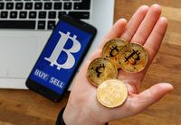 human's hand holding gold coin of Bitcoin and Virtual currency symbol on mobile app screen with big