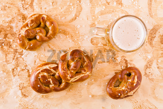 Several salty cooked pretzel and lager beer seen from above