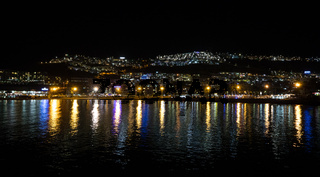 Night photography of the city with blue and yellow lights reflecting in the ocean. Puerto Rico, Gran Canaria, Spain.
