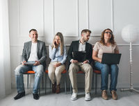 Group of young creative people sitting on chairs in waiting room