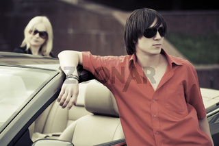 Young fashion couple at the convertible car