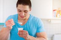 Junger Mann isst essen Joghurt in der Küche gesunde Ernährung Frühstück