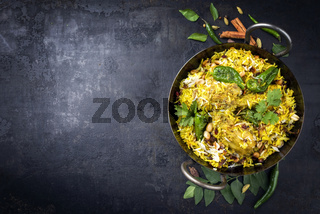 Traditional Indian chicken biryani with nuts and raisins as close-up in a korai with copy space left