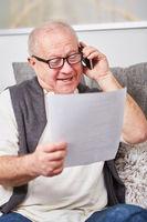 Rentner mit Dokument beim Telefonieren