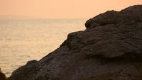 Sunset over the ocean, rock in front of sea surface and sky full of warm sunlight