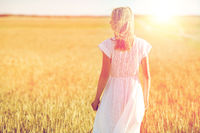 young woman in white dress on cereal field
