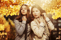 Two young fashion teen girls in autumn park